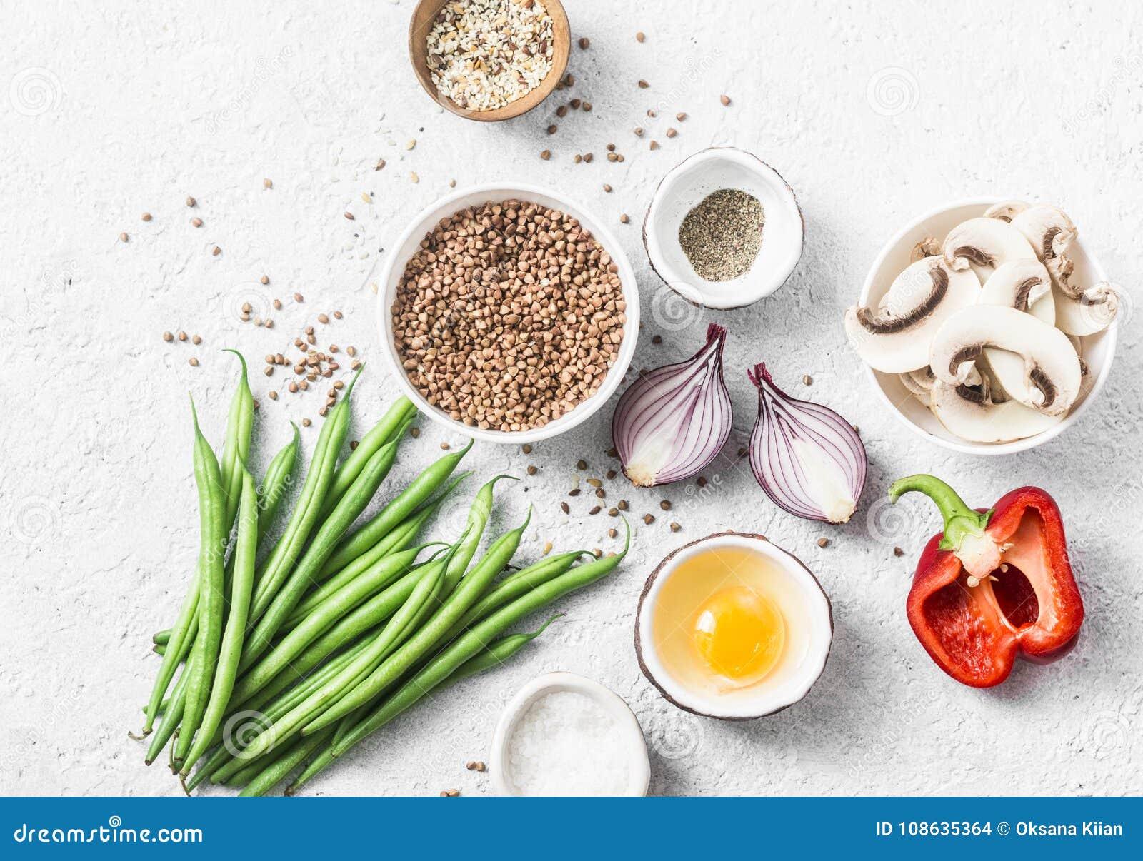 Vlak leg gezonde vegetarische voedselingrediënten voor lunch op een lichte achtergrond, hoogste mening Boekweit, slabonen, rode p