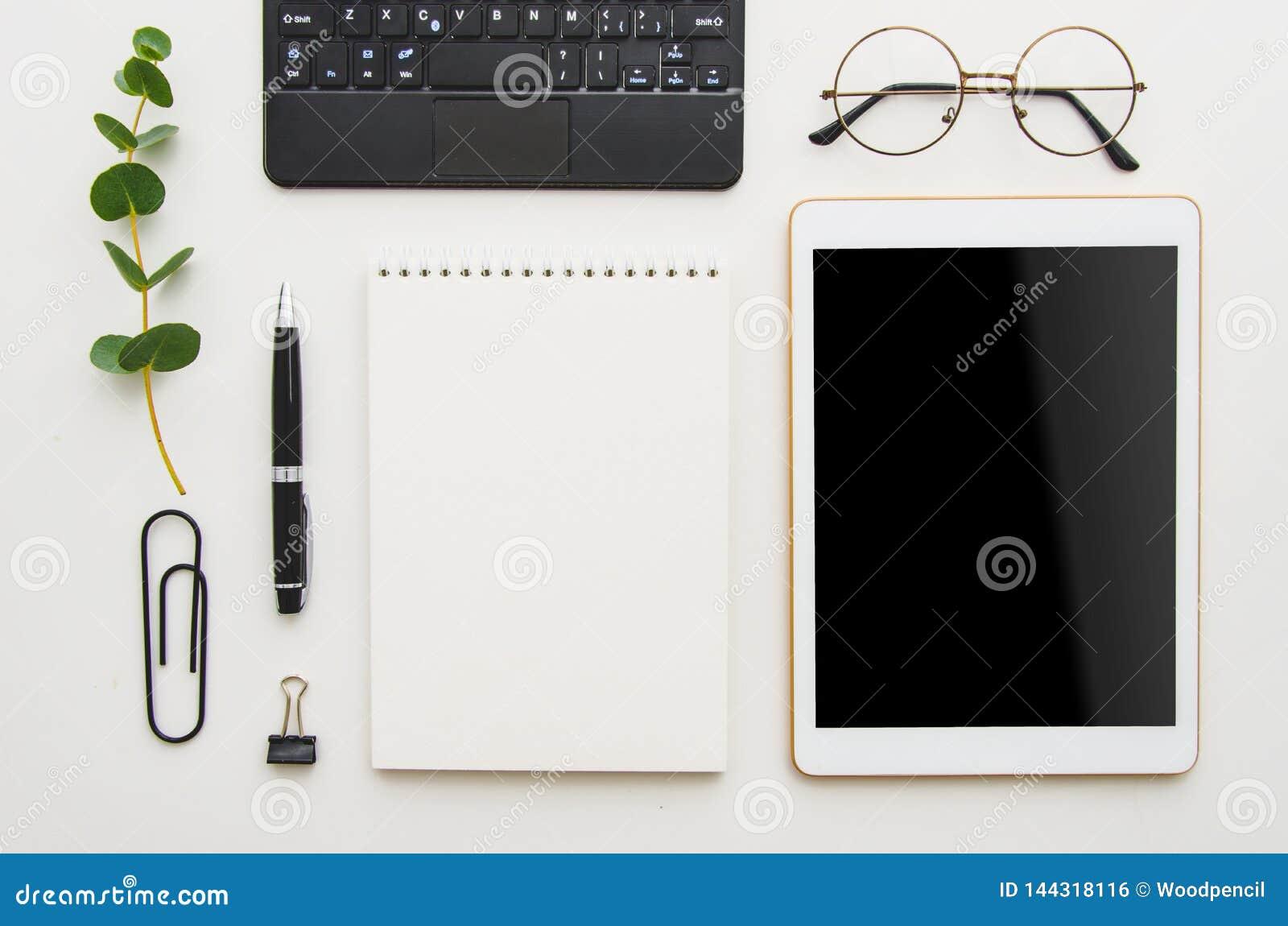 Vlak leg het werkplaats Witte bureaulijst met laptop, klemmen, glazen, notitieboekje en pen Hoogste mening met exemplaarruimte