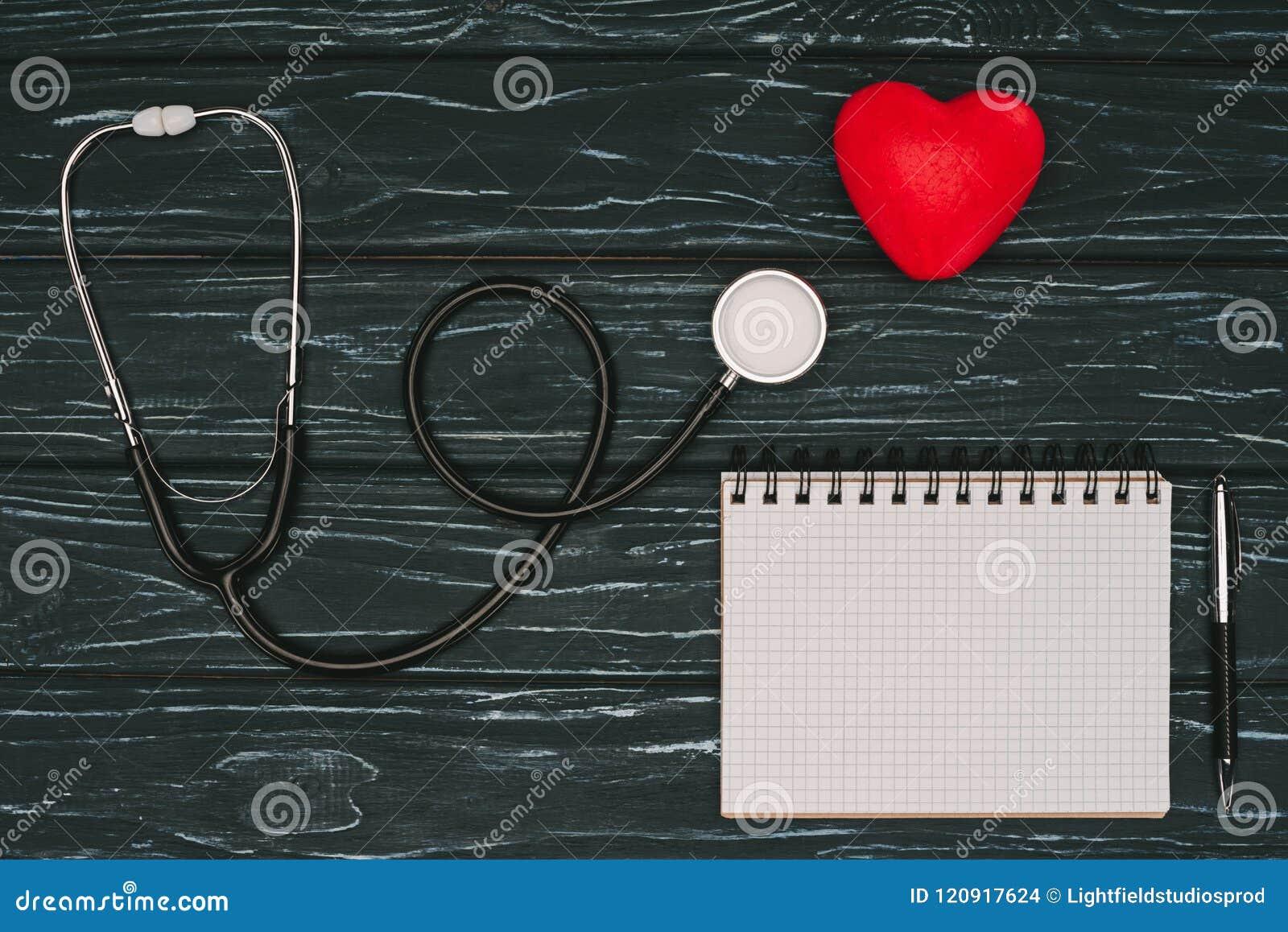 Vlak leg met geschikt rood hart, stethoscoop en leeg notitieboekje op donker houten tafelblad, wereldgezondheid