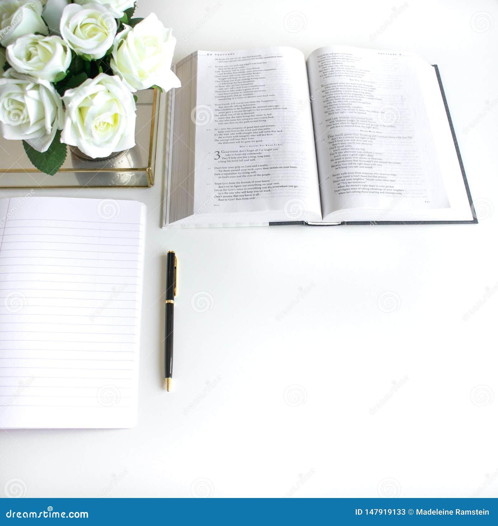 Vlak leg met verschillende toebehoren; bloei boeket, roze rozen, open boek, Bijbel