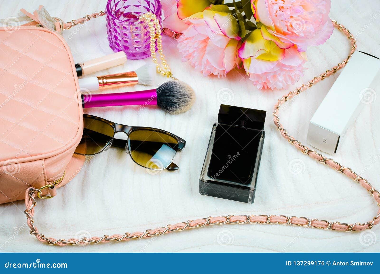 Vlak leg met vrouwelijk zak, schoonheidsmiddelen, zonnebril, parfume en gezichtspoeder Manierconcept op witte achtergrond