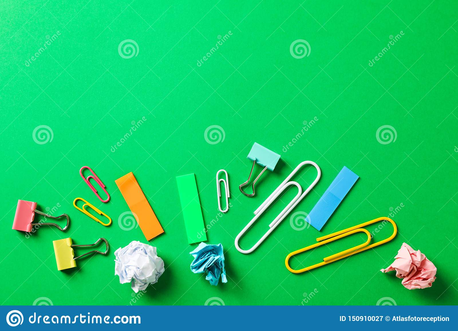 Vlak leg samenstelling met verfrommelde document ballen, klemmen en stickers op kleurenachtergrond