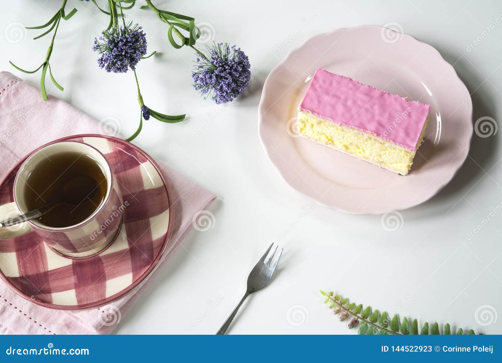 Vlak leg typisch Nederlands zoet roze verglaasd gebakje tompouce op roze plaat Met kop thee
