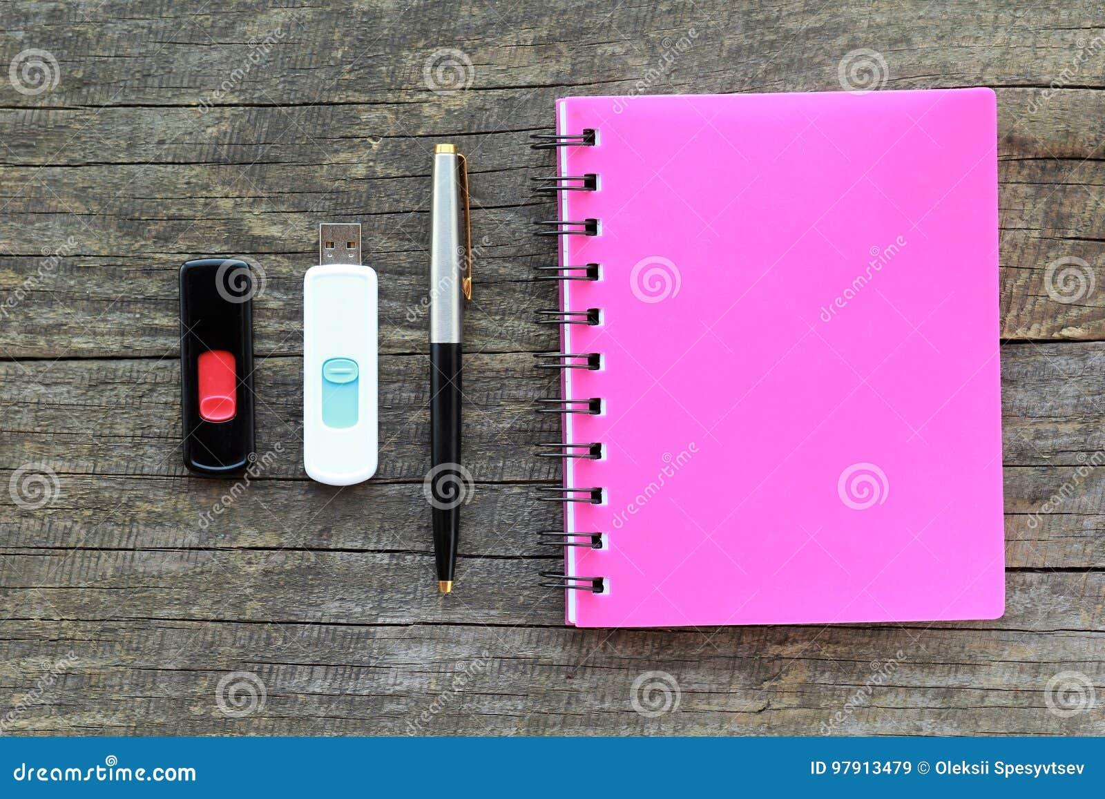 Vlak leg van kantoorbehoeften, namelijk roze begrensd notaboek, pen en twee aandrijving van de usbflits op grijze houten lijst