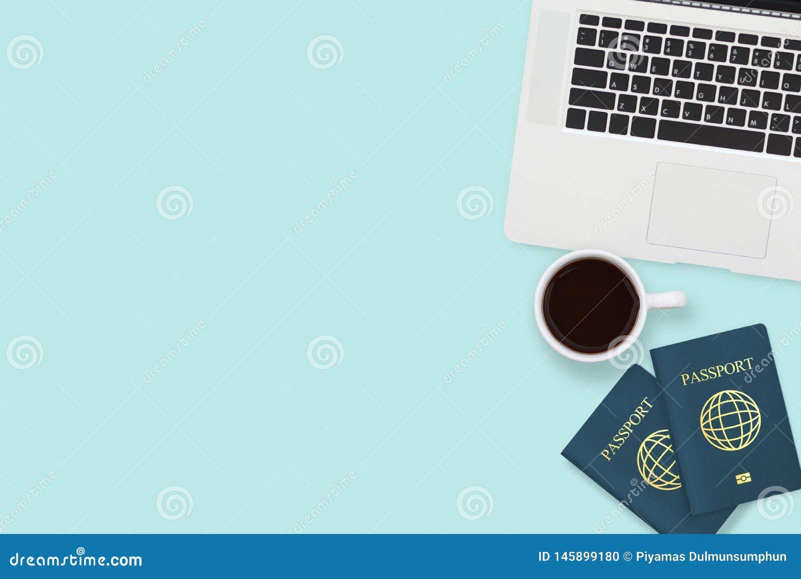Vlak leg van paspoort twee, koffiekop en computerlaptop op achtergrond van de pastelkleur de blauwe kleur met exemplaarruimte rei