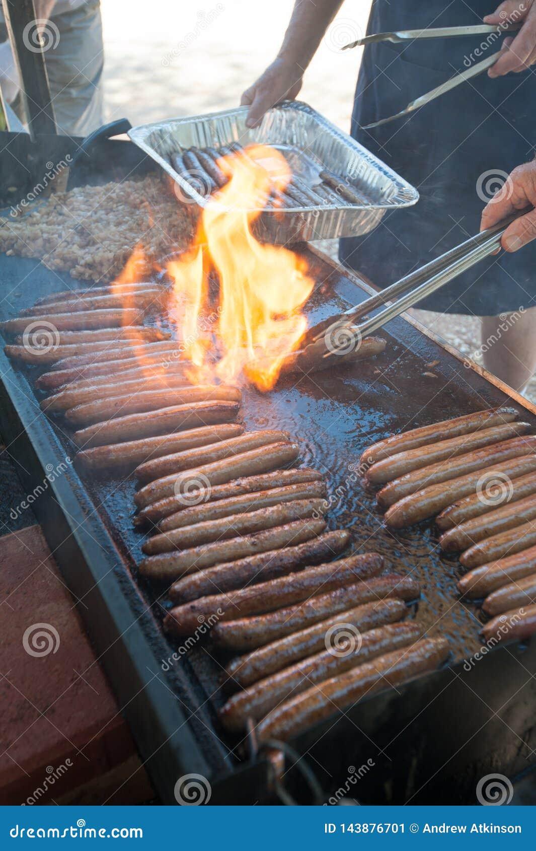 Vlammen die omhoog op de warmhoudplaat met worsten en uien flakkeren