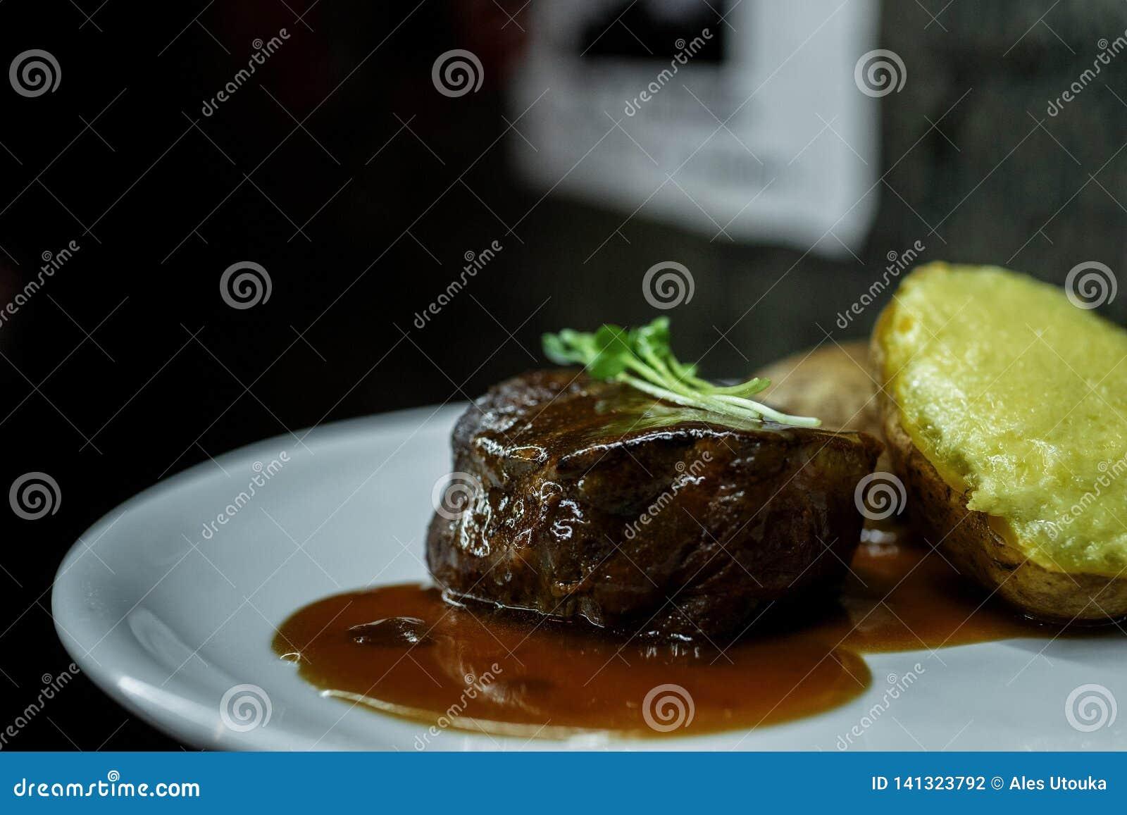 Vlees van het close-up het sappige geroosterde lapje vlees met barbecuesaus en gevulde aardappels op een plaat in een restaurant