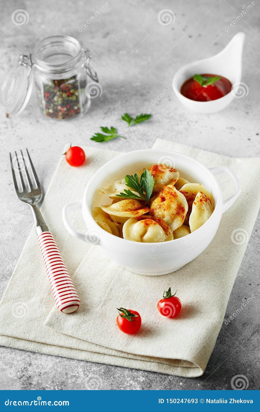 Vleesbollen - Russische pelmeni, ravioli met vlees op een witte kom