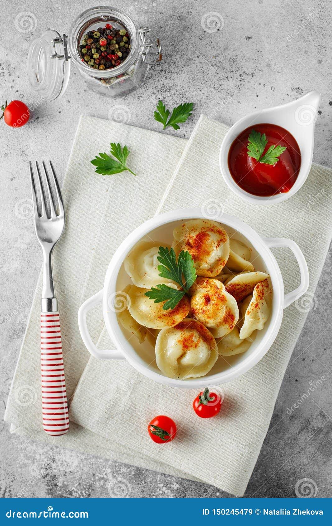Vleesbollen - Russische pelmeni, ravioli met vlees op een witte kom Vlak leg samenstelling
