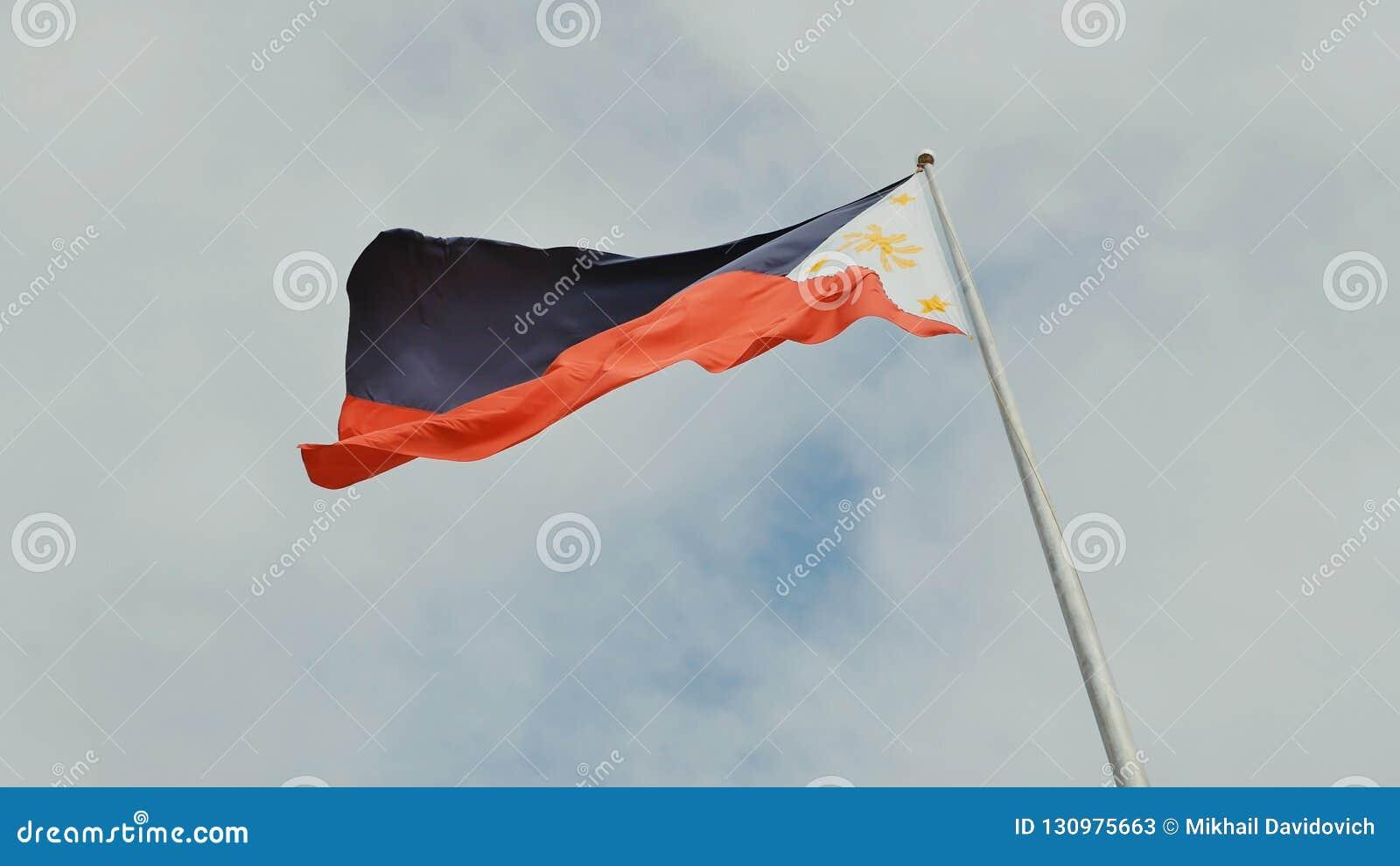 Vliegende tweekleurige vlag van de Filippijnen met centrale gouden zon die de provincies en de sterren vertegenwoordigen de eilan