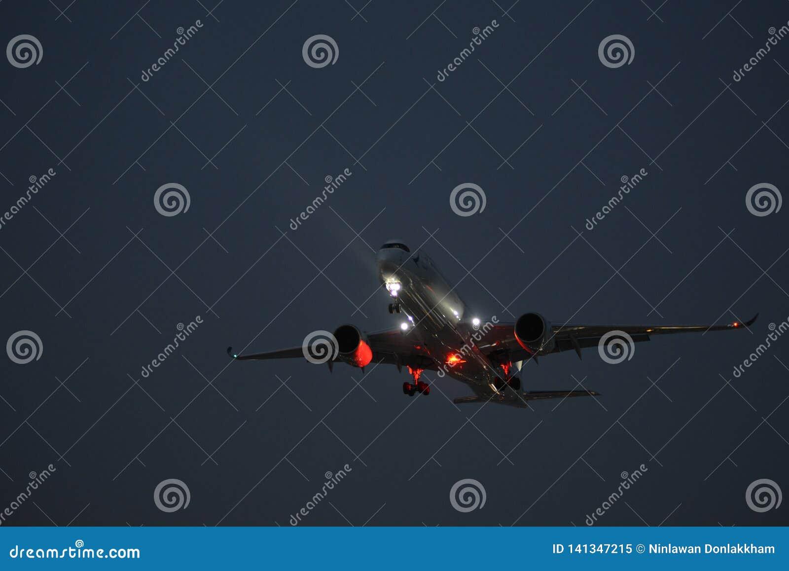 Vliegtuig die bij het vallen van de avond landen