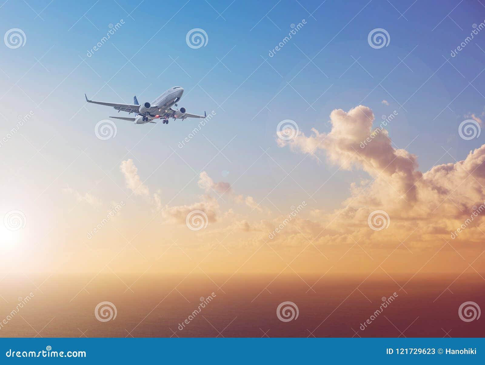 Vliegtuig die boven oceaan met de achtergrond van de zonsonderganghemel vliegen - trav