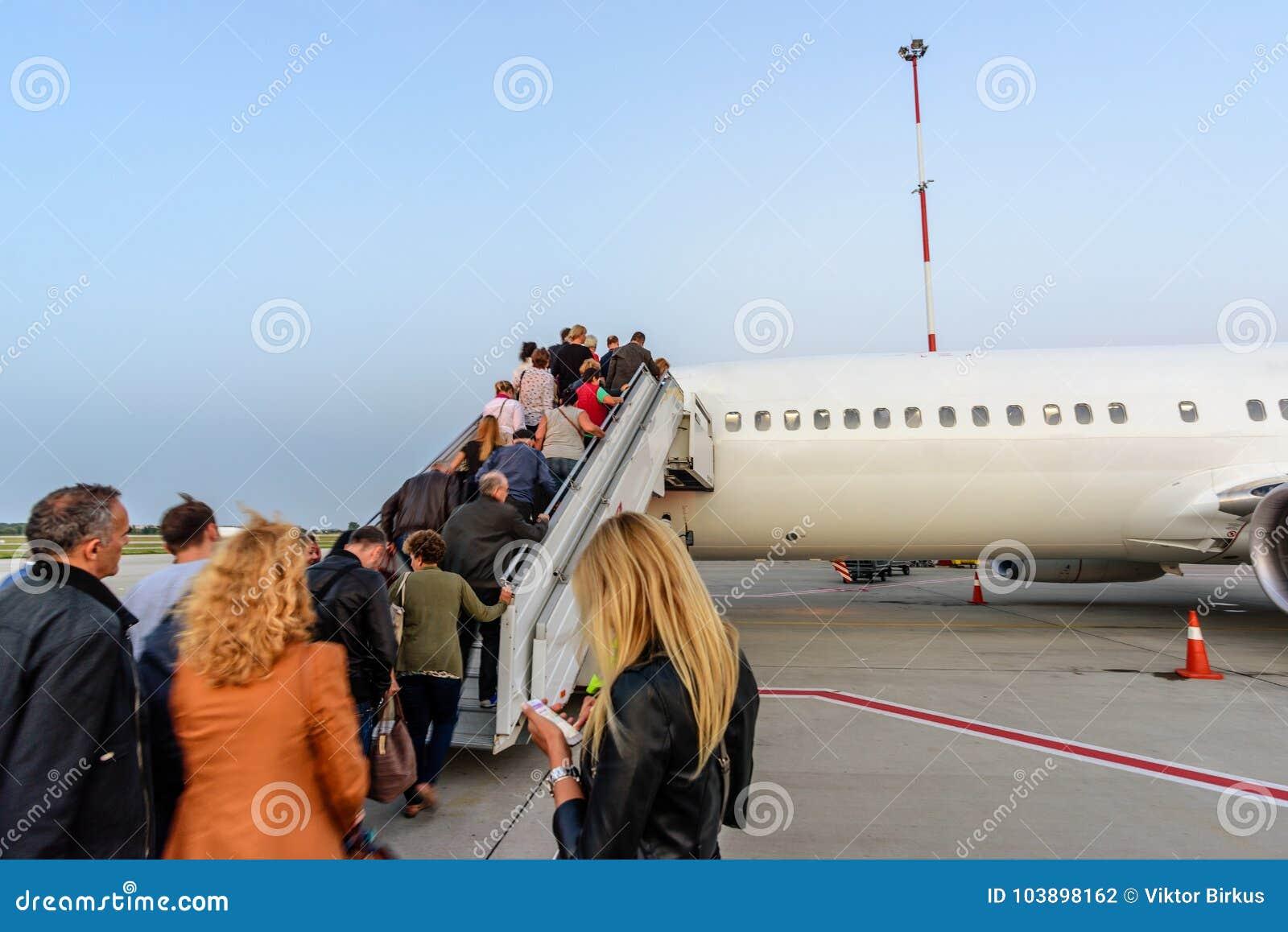 Vliegtuig in luchthaven klaar aan het vliegen en mensen het uitgaan