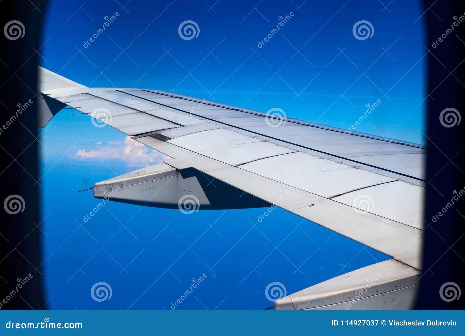 Vliegtuigvleugel in blauwe hemel, mening door vliegtuigvenster Reis door de lucht De mening van het vliegtuigenvenster