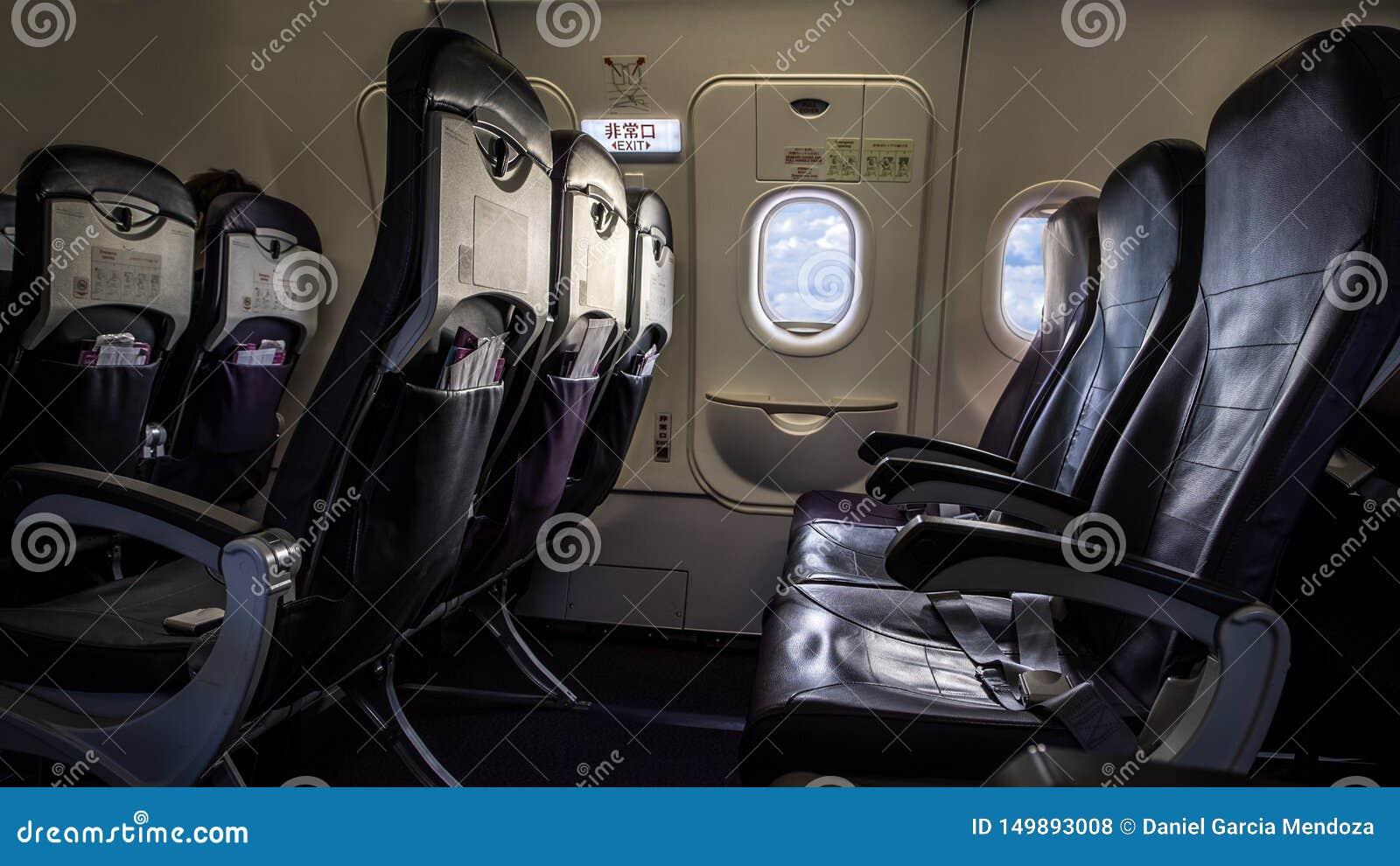 Vliegtuigzetel en vensters binnen een vliegtuig De passagiersvenster van het wolkenvliegtuig