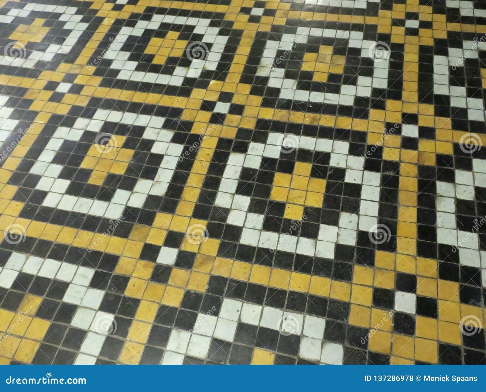 Vloer van gele zwart-witte tegels die kruisen en een bewegend patroon vormen