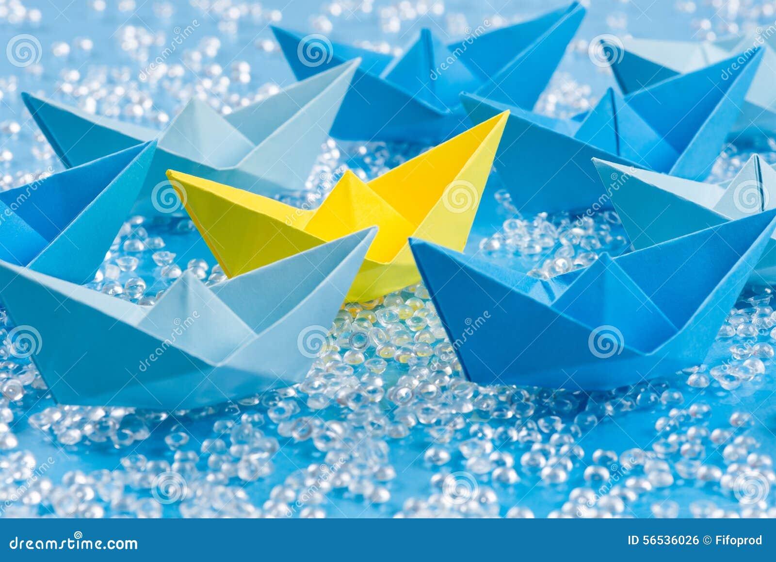 Vloot van blauwe Origamidocument schepen op blauw water zoals achtergrond die gele omringen