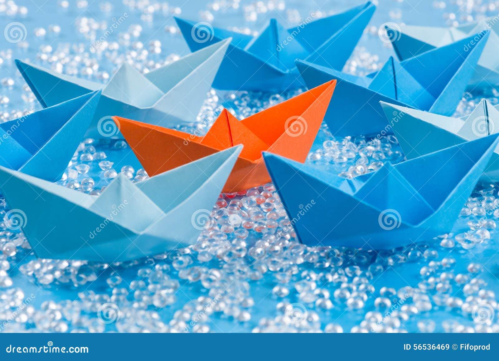 Vloot van blauwe Origamidocument schepen op blauw water zoals achtergrond die oranje omringen