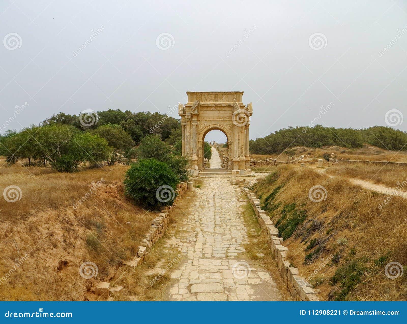 Voûte triomphale de Roman Emperor Septimius Severus à Leptis Magna avec le ciel obscurci flou et l herbe sèche