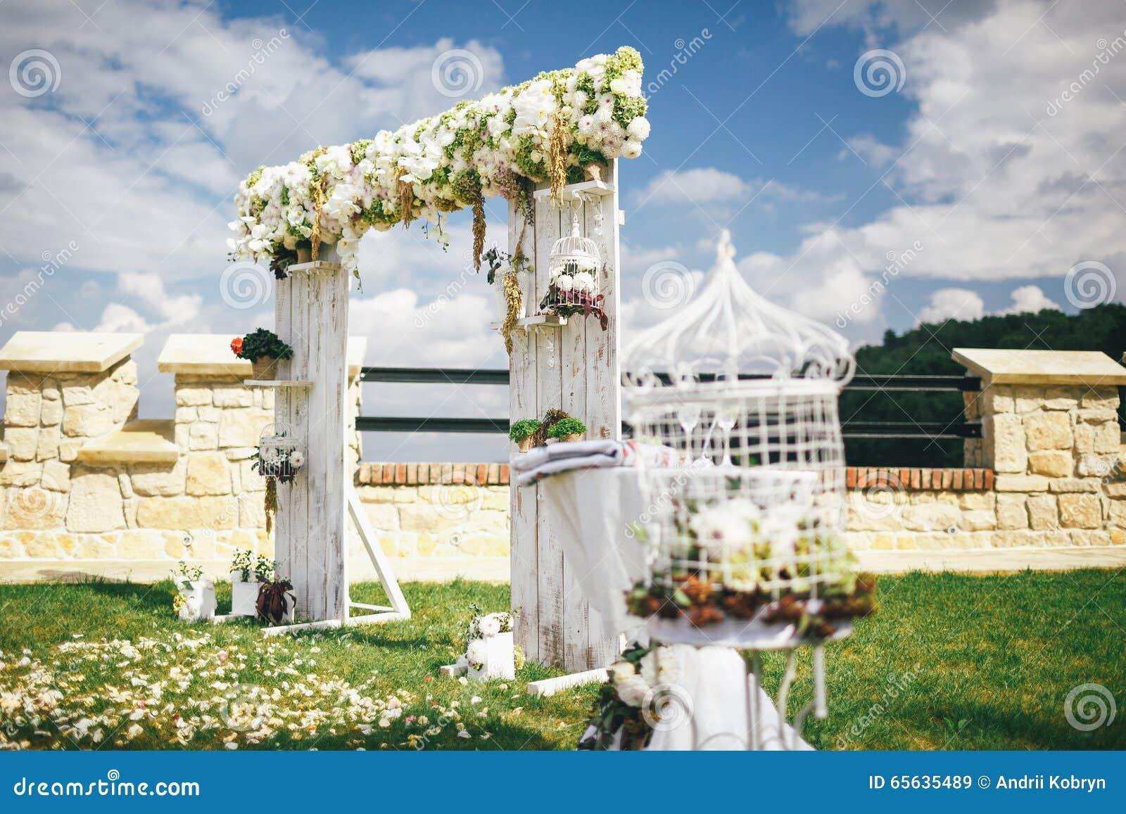 Voûte de mariage décorée des fleurs sous le ciel bleu avec des nuages
