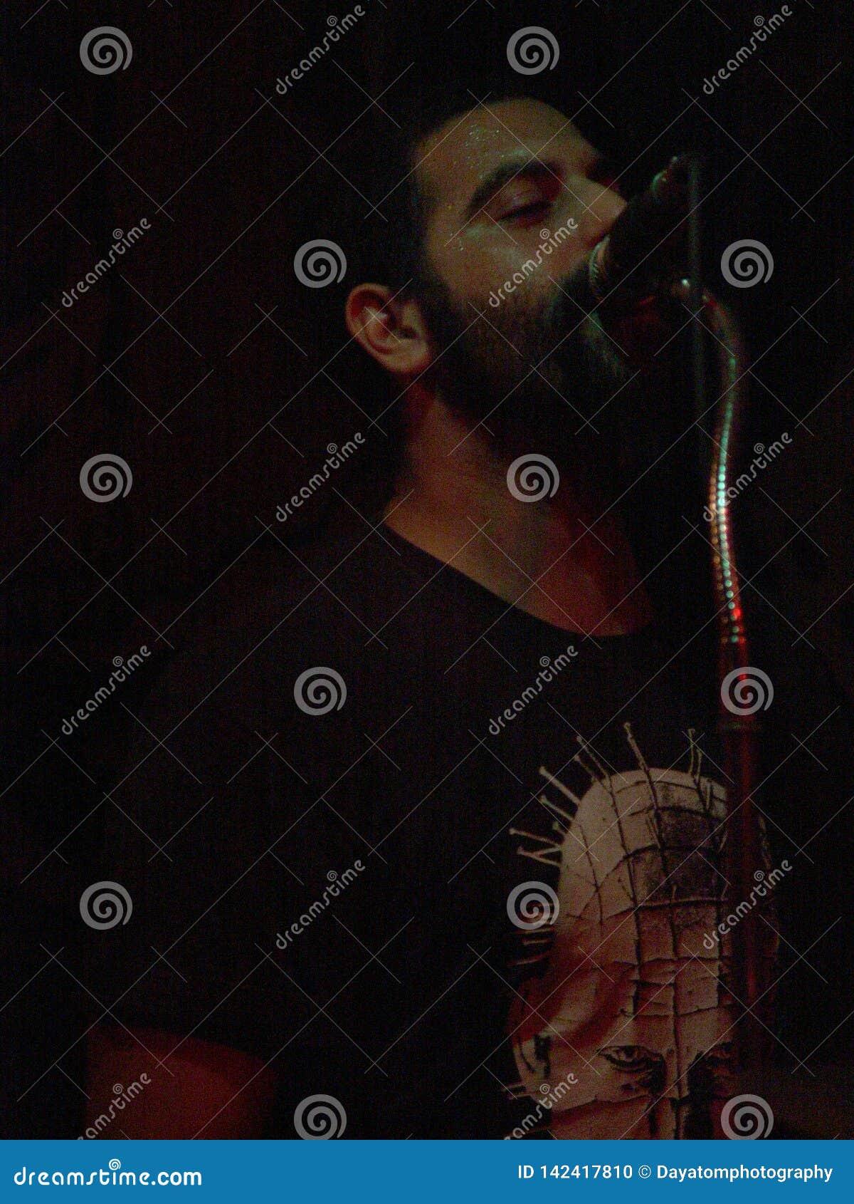Vocalista masculino da rocha que canta perto de um microfone em uma mostra na noite em arredores escuros