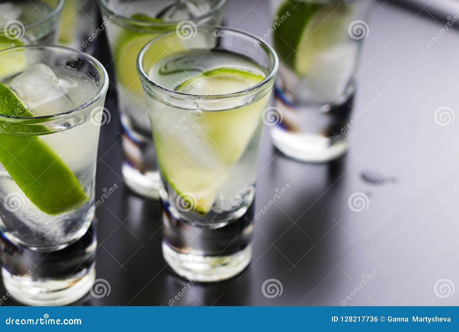 Vodka, tequila, gin, alkoholcoctail med is och limefrukt på en svart bakgrund En restaurang stång Ett parti