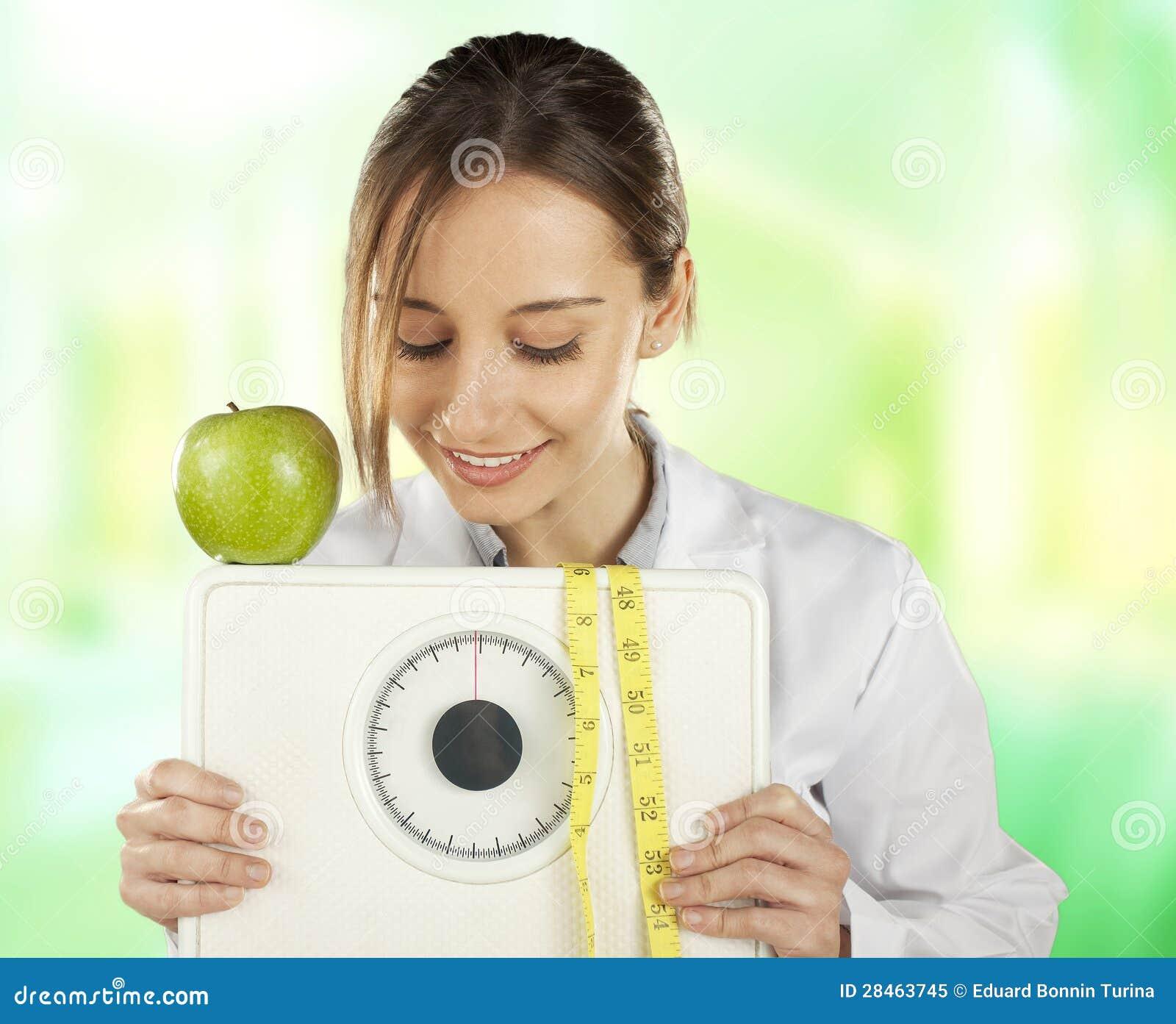 Voedingsdeskundige die en op een gewichtsschaal en op een groene appel let houdt