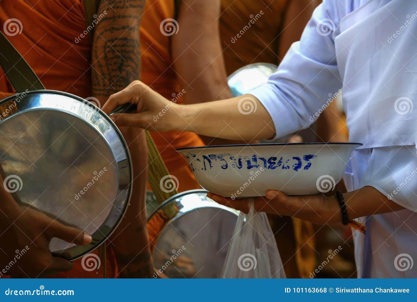 Voedsel die door boeddhistisch Thais wijfje aan de monnik aanbieden