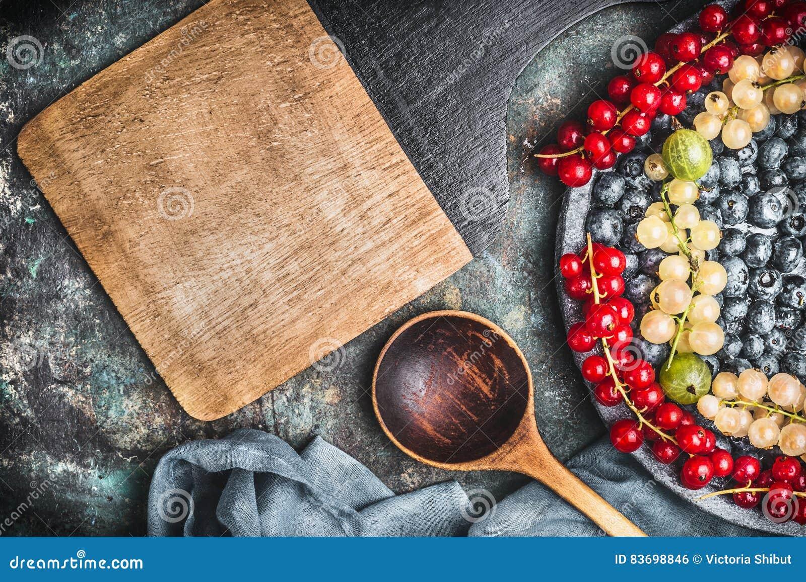 Voedselachtergrond voor gezonde recepten met diverse kleurrijke bessen, kokende lepel, kommen en servet, hoogste mening