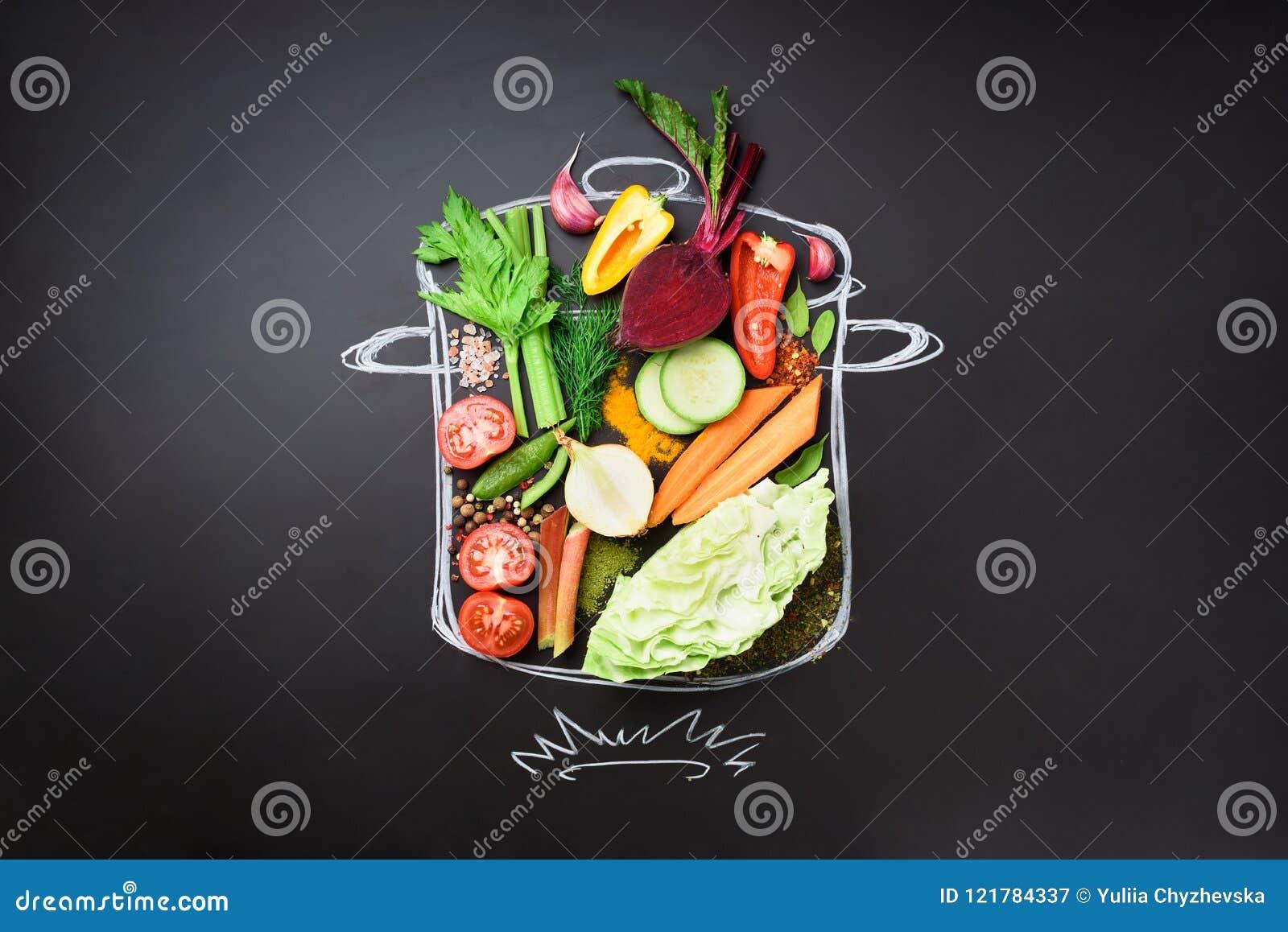 Voedselingrediënten voor het mengen van romige soep op geschilderde stewpan over zwart bord Hoogste mening met exemplaarruimte or