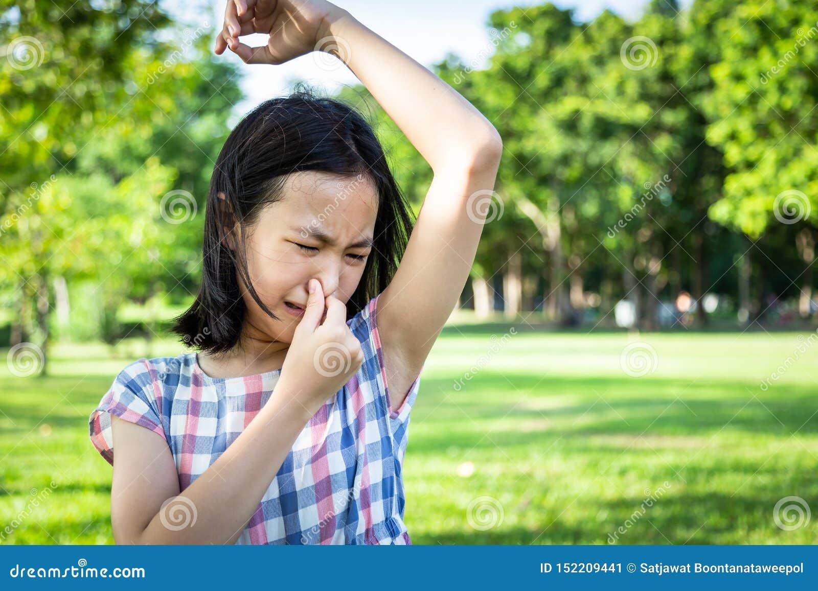 Voelt het close-up Aziatische leuke meisje slechte vuile geursituatie, ruiken, die haar natte oksel in openluchtpark, mooi kind s