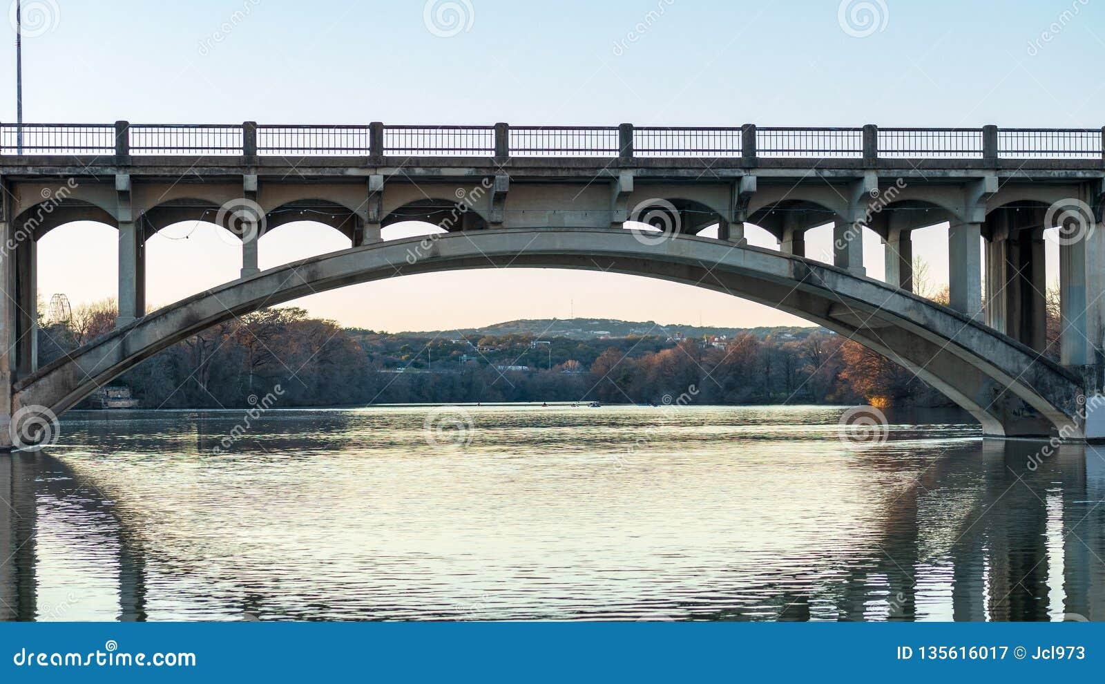 Voertuig en voetgangersoversteekplaatsbrug die over een rivier tijdens gouden uur overspannen