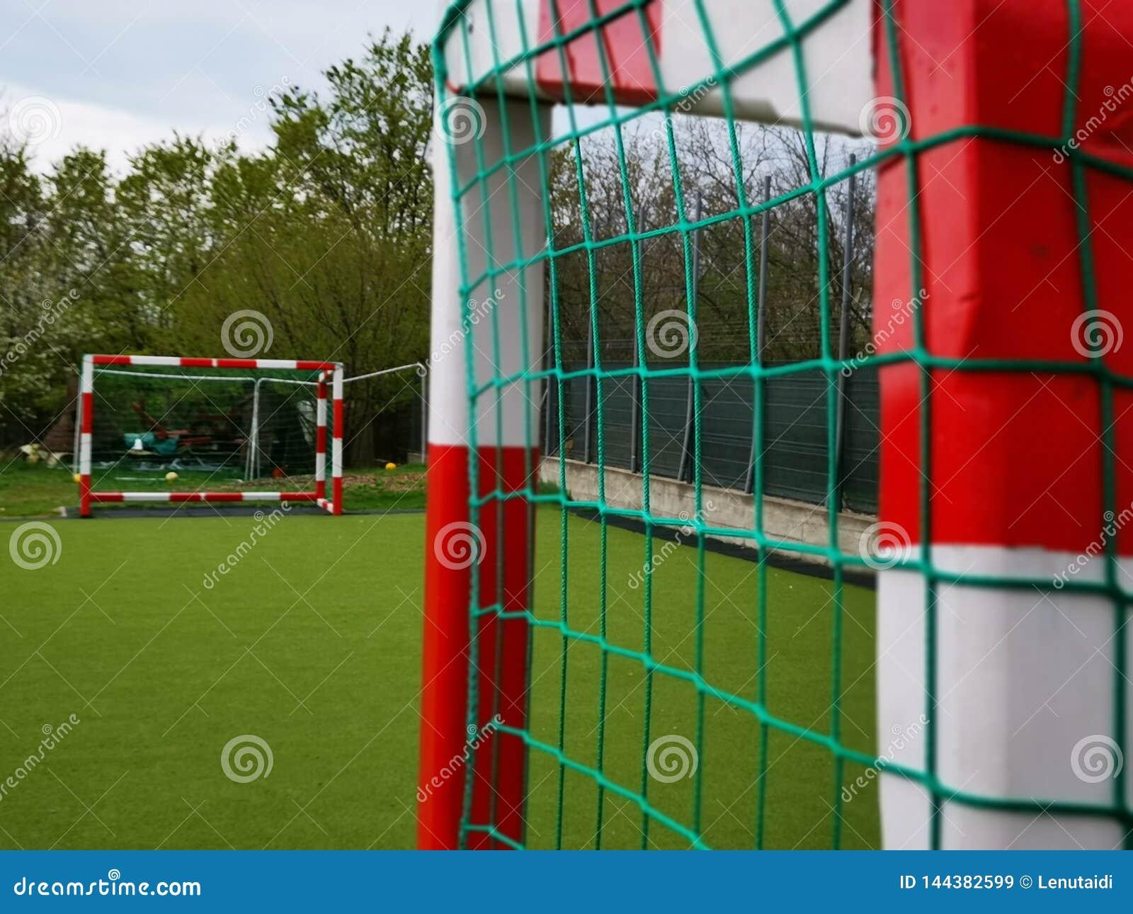 Voetbalpoorten in rood worden geschilderd die en wit