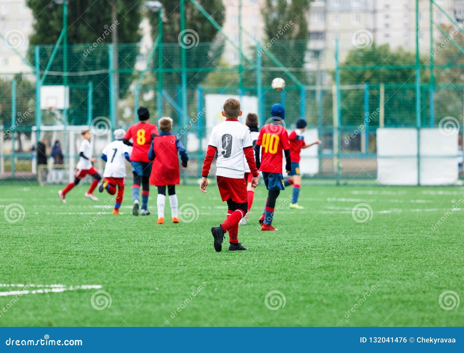 Voetbalteams - jongens in rood, blauw, wit eenvormig spelvoetbal op het groene gebied jongens het druppelen Teamspel, opleiding,