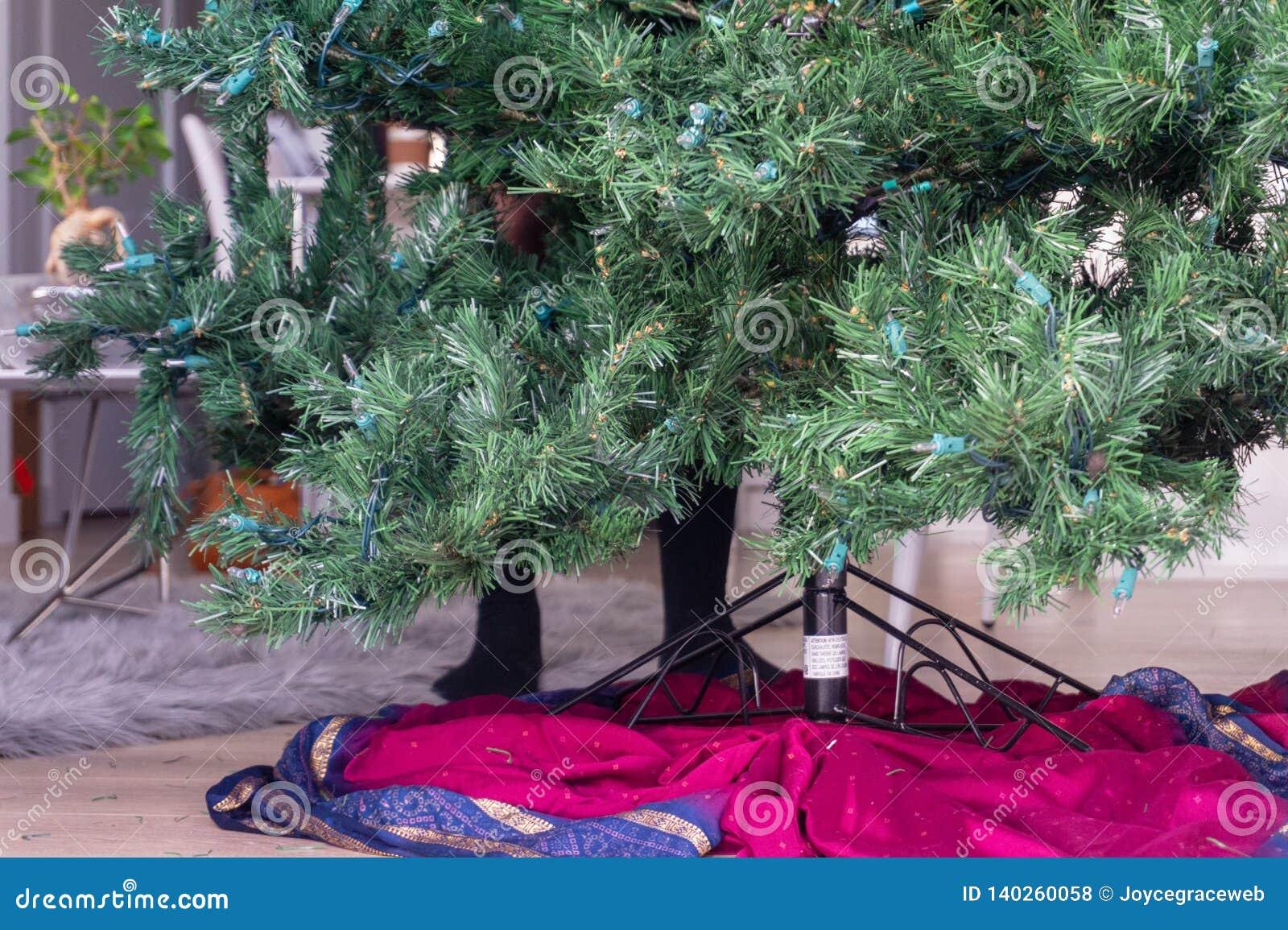 Voeten achter een kunstmatige Kerstboom