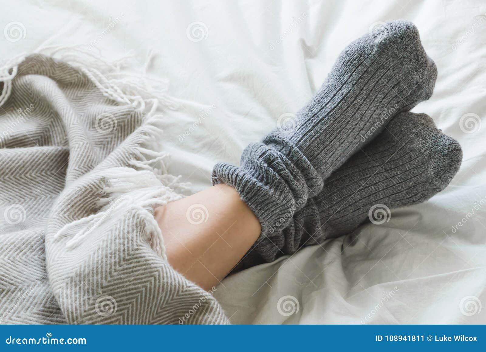 Voeten met grijze sokken op bed onder deken worden gekruist die