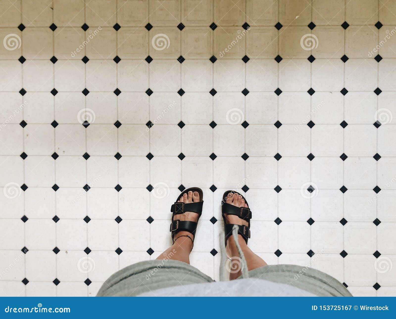 Voeten van een persoon in sandals op witte tegels in een badkamers
