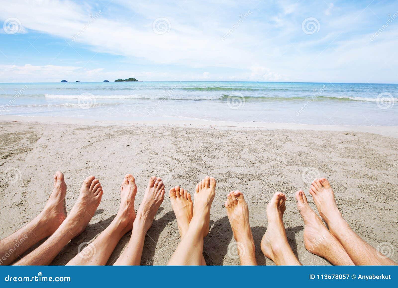Voeten van familie of groep vrienden op het strand, vele mensen die samen zitten