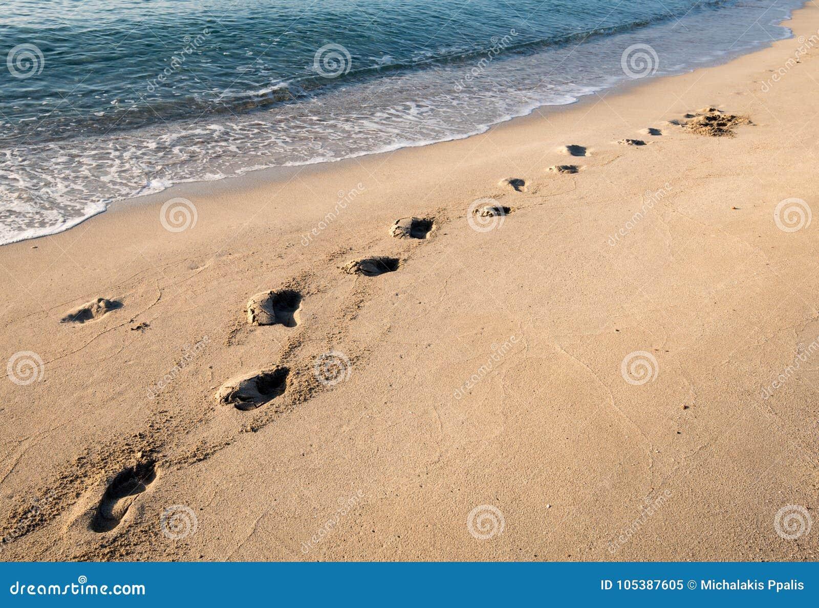 Voetstappen op een zandig strand
