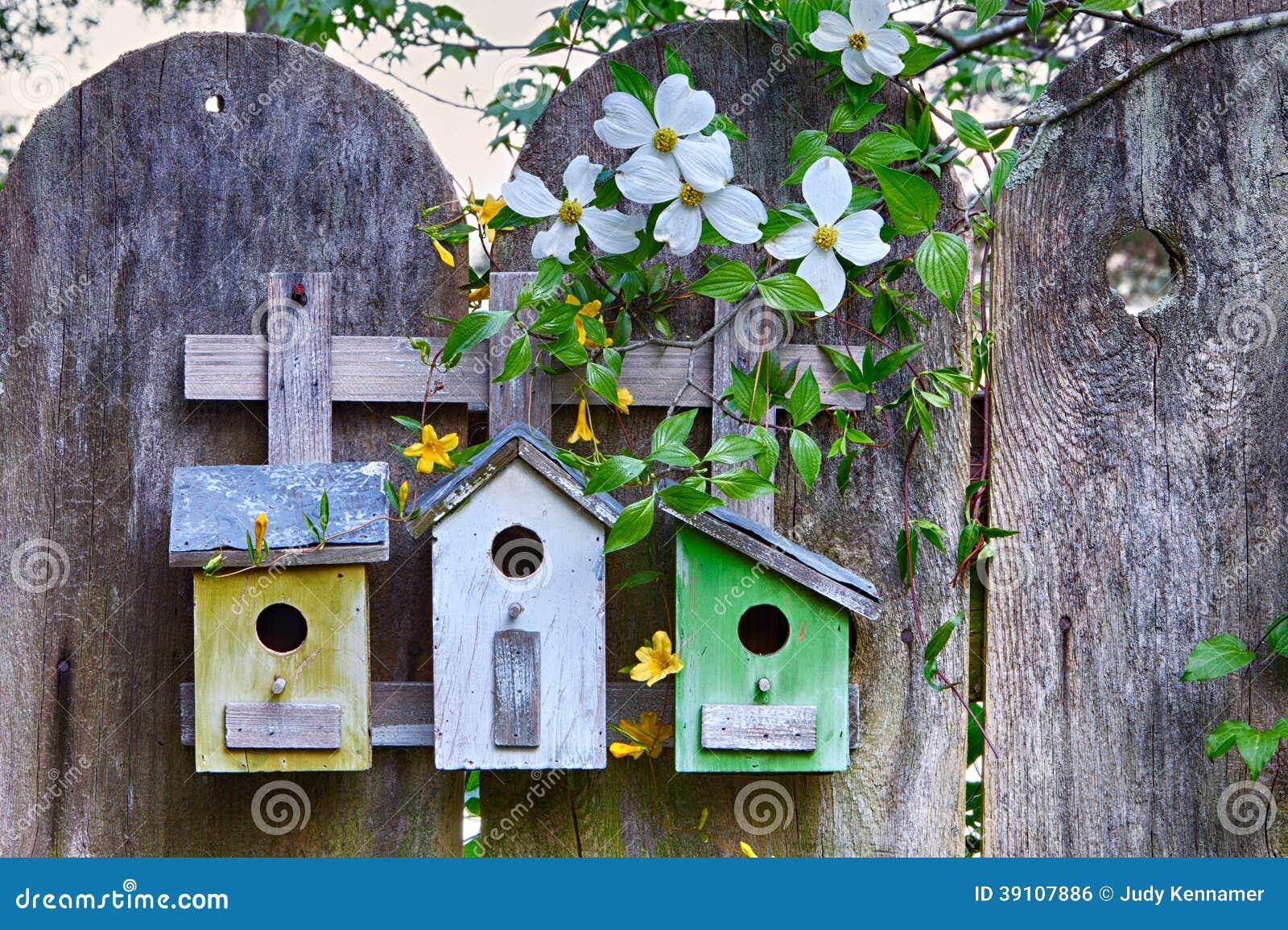 Vogelhuizen op houten omheining met bloemen