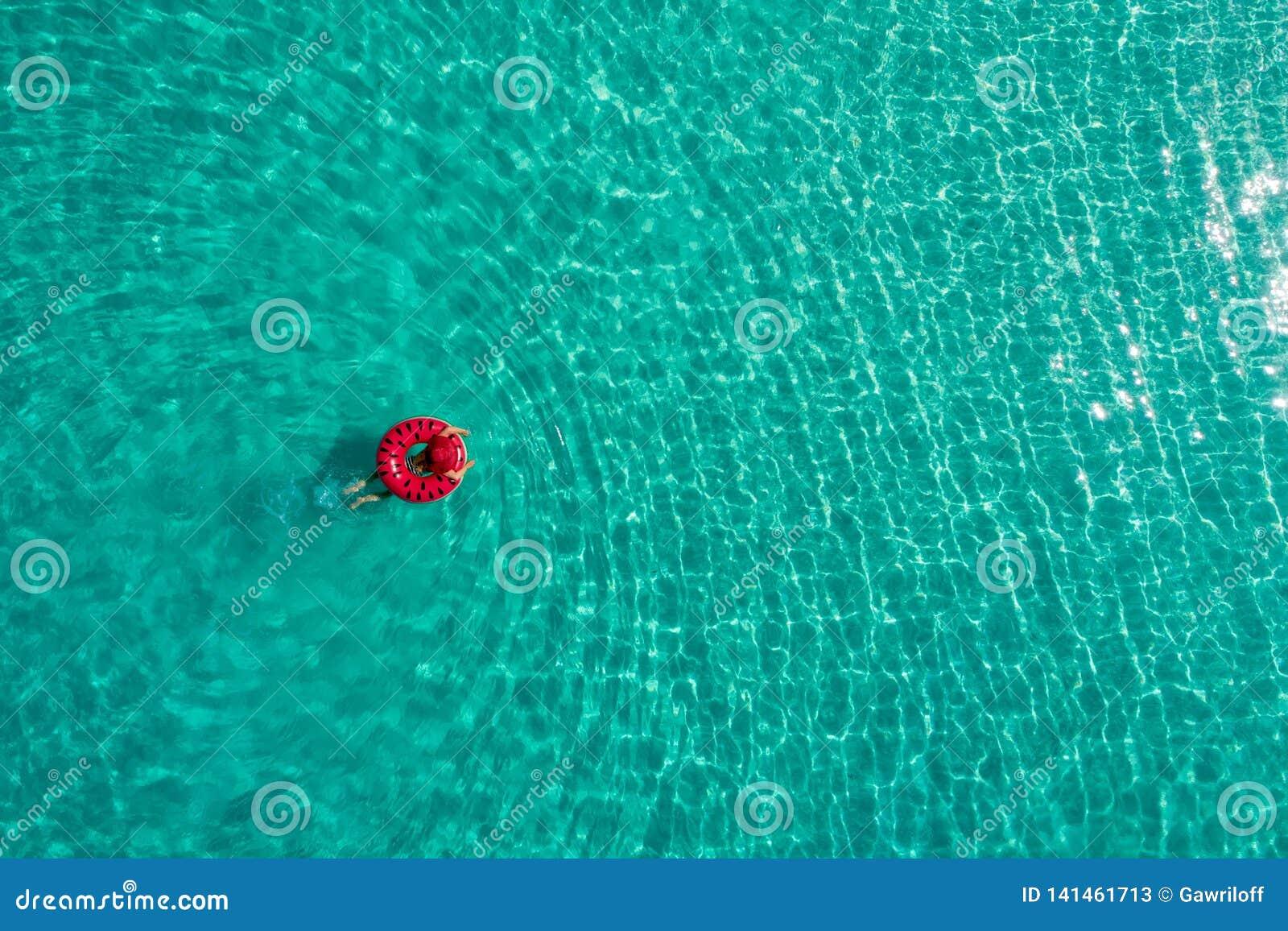 Vogelperspektive der dünnen Frauenschwimmens auf dem Schwimmenringdonut im transparenten Türkismeer in Seychellen Sommermeerblick