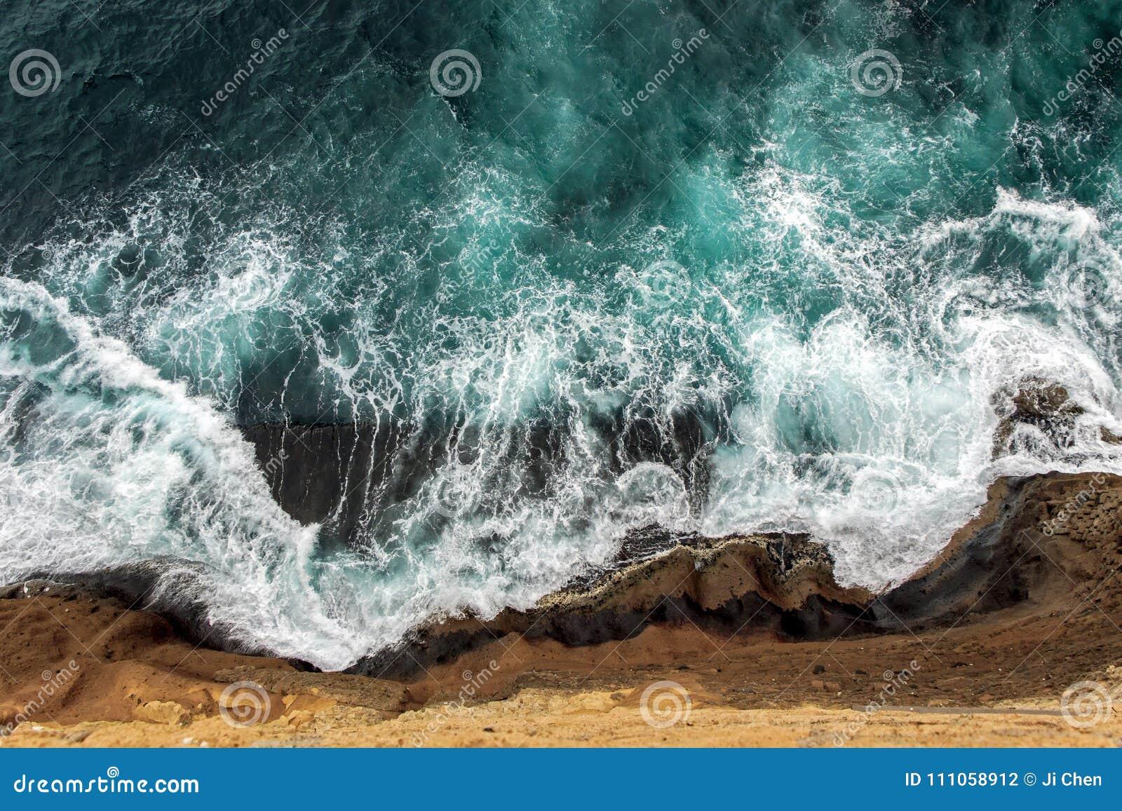 Vogelperspektive von Meereswogen auf Klippe