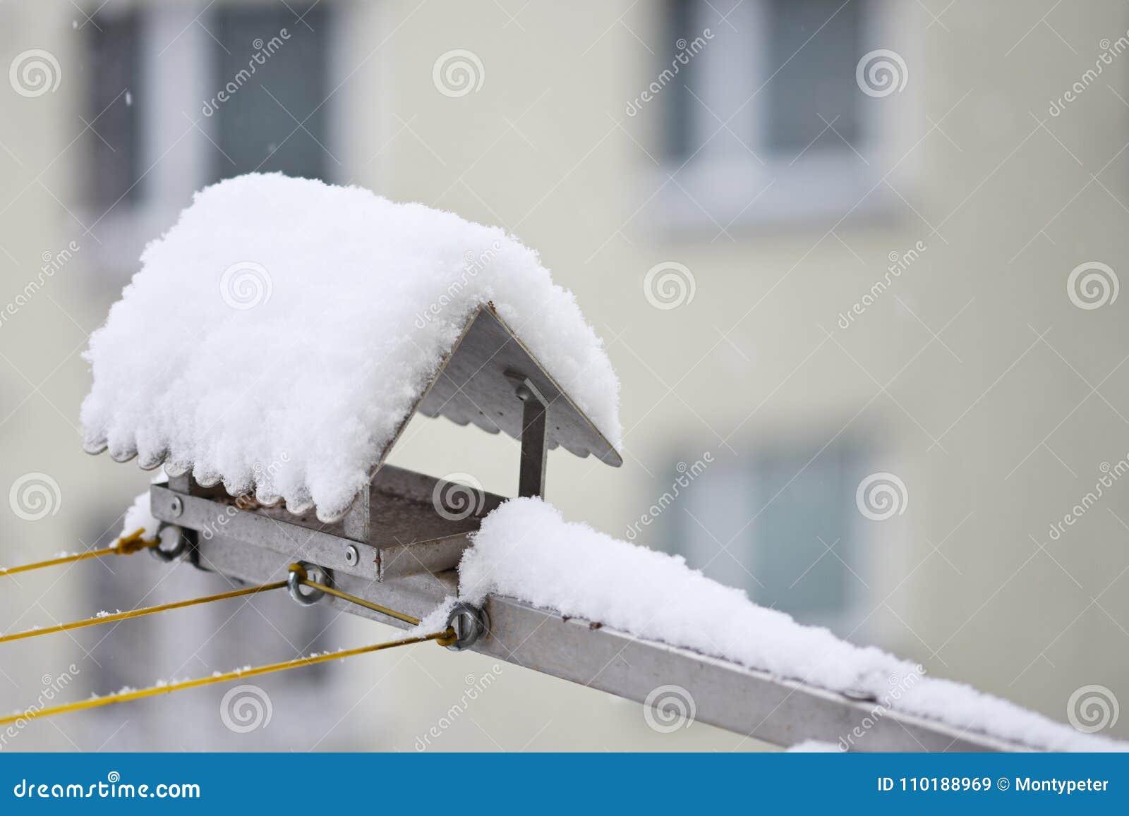 Een Winters Balkon : Vogelvoeder in de winter met sneeuw huis op het balkon stock