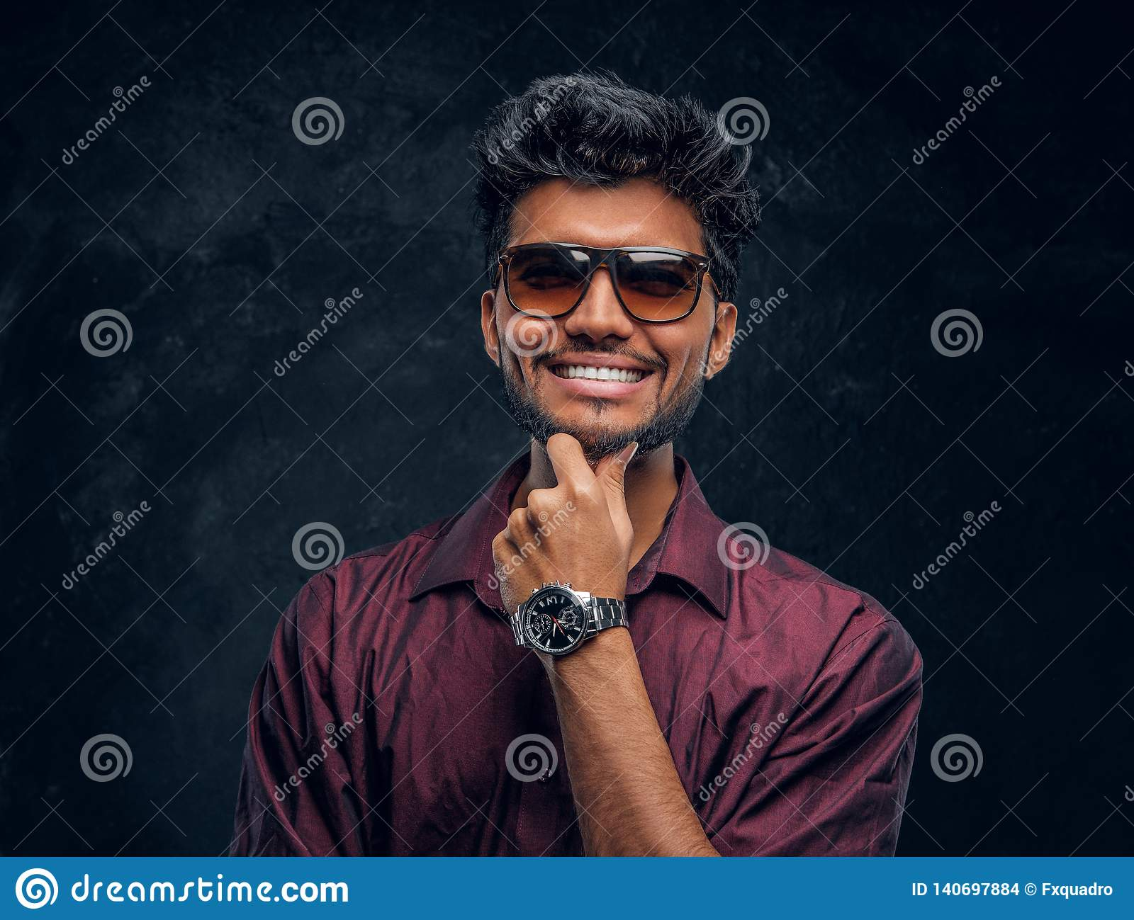 Vogue, fashion, style. Cheerful young Indian guy wearing a stylish shirt and sunglasses posing with hand on chin.