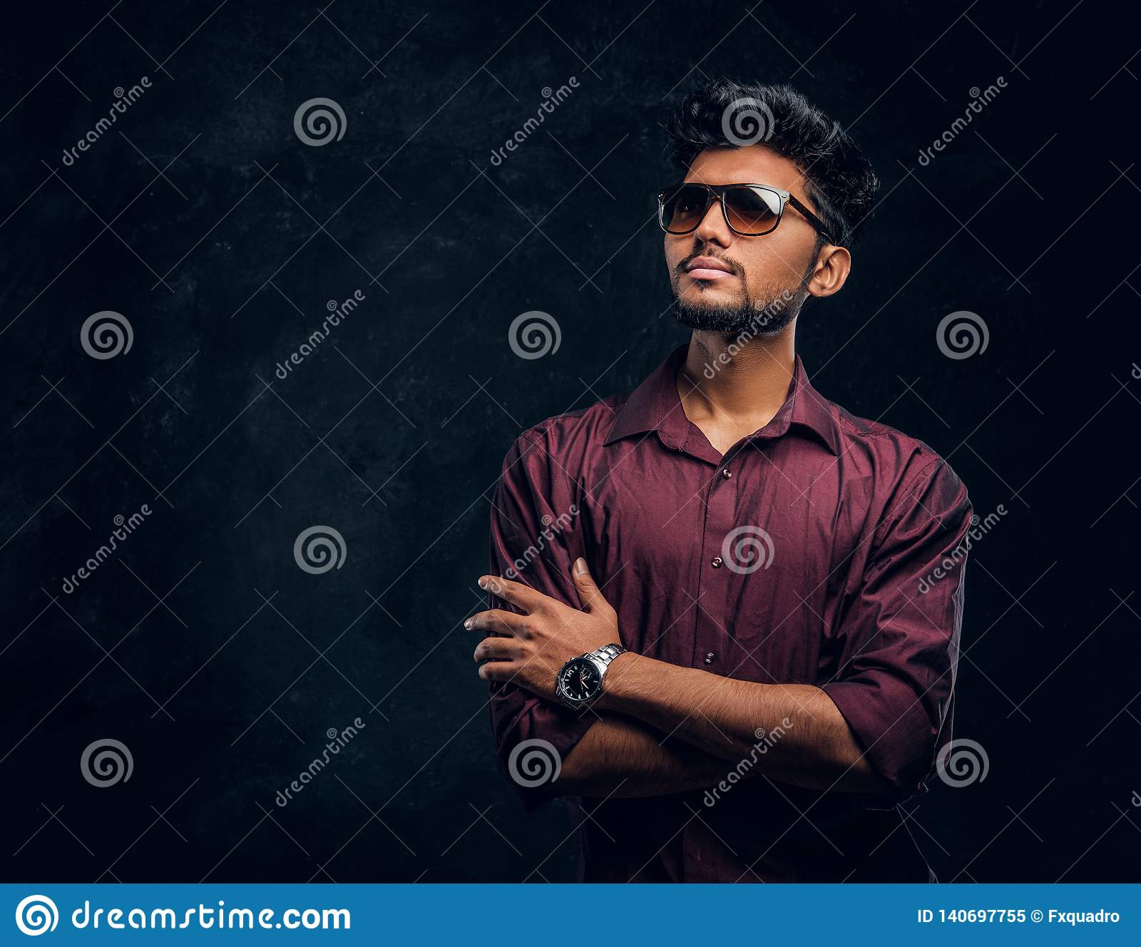 Vogue, fashion, style. Handsome young Indian guy wearing a stylish shirt and sunglasses posing with crossed arms.