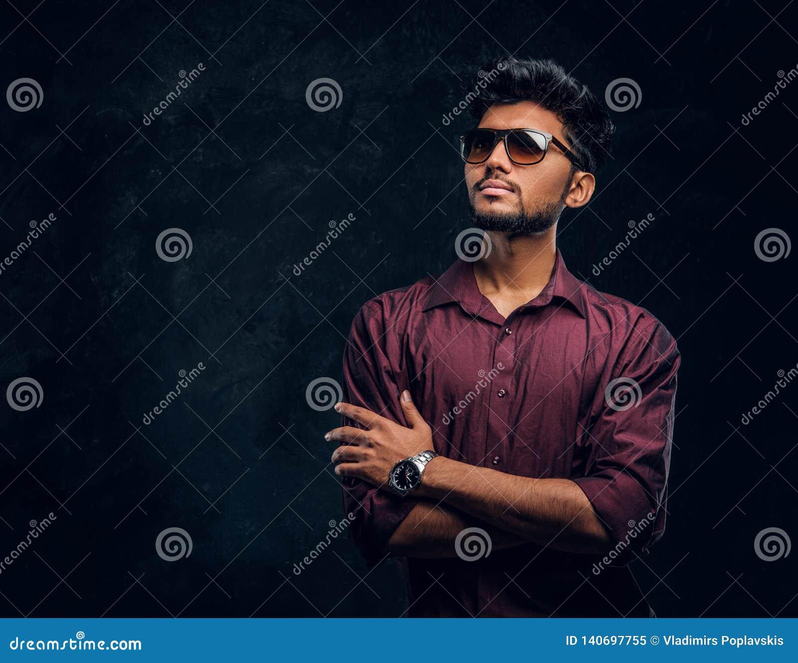 Vogue, manier, stijl Knappe jonge Indische kerel die een modieus overhemd en zonnebril dragen die met gekruiste wapens stellen