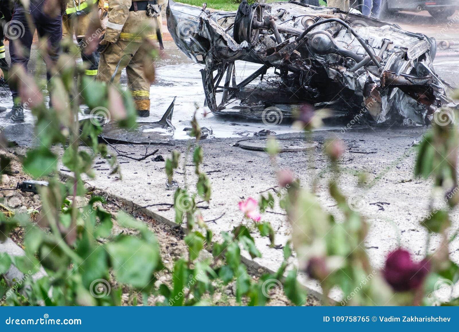 Voiture brûlée après un accident sur la route Sapeurs-pompiers se tenant tout près Photo de reportage