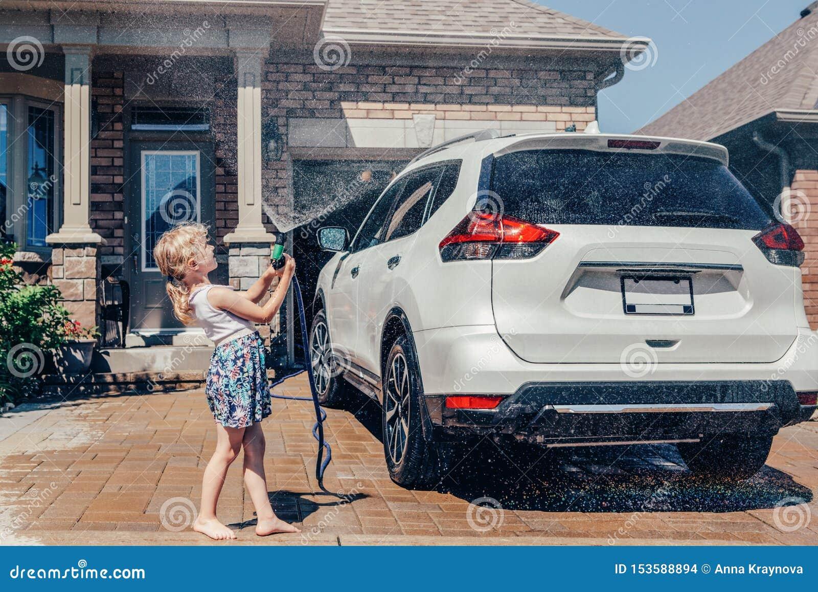 Voiture de lavage de fille sur l allée dans la maison avant le jour ensoleillé d été