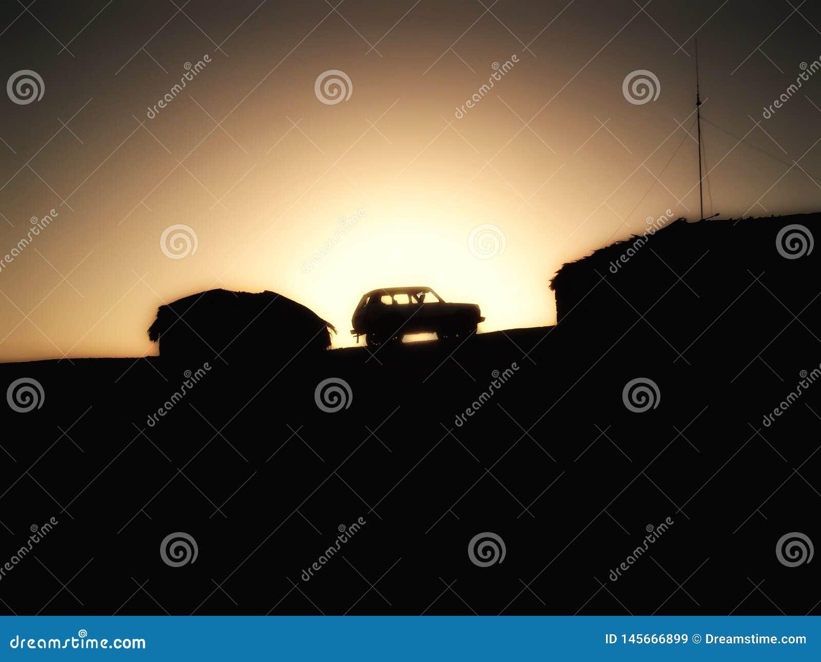 Voiture entre les cabanes dans les montagnes au coucher du soleil