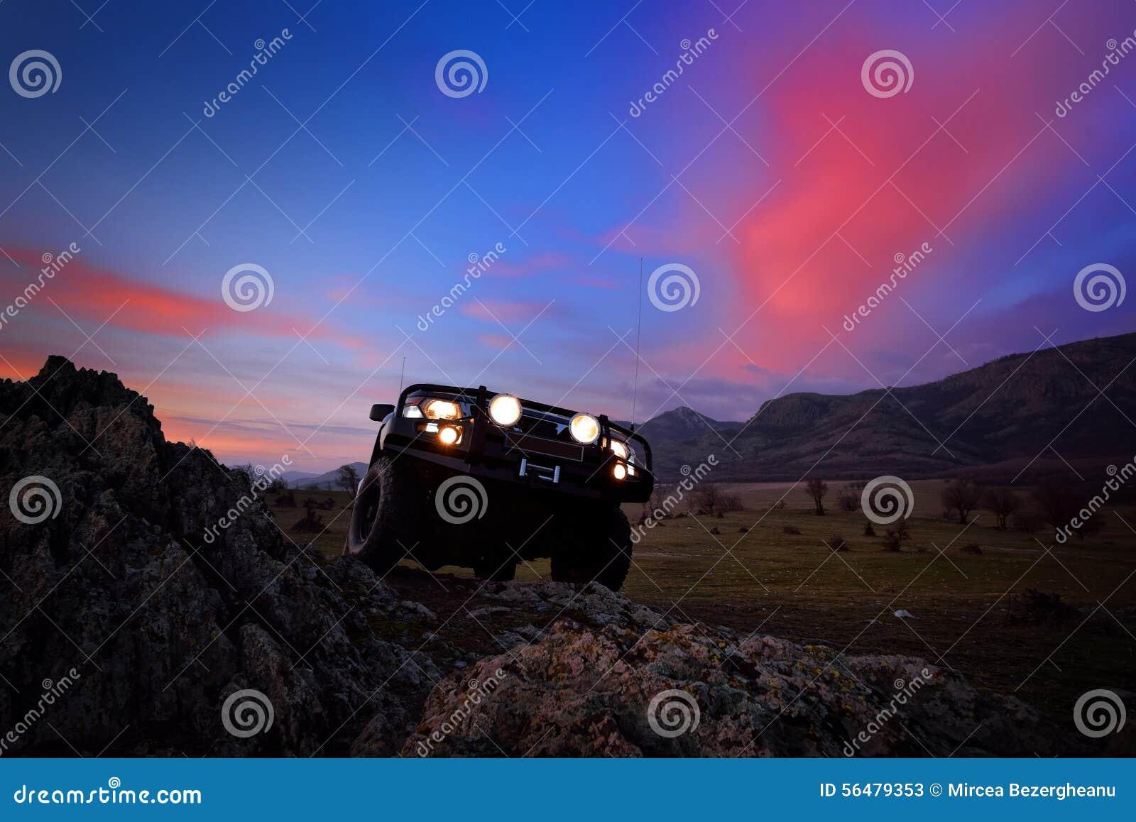 Voiture tous terrains sur la route de montagne au coucher du soleil